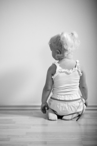 little girl sits on her knees facing the wall