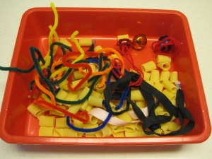 Pipe cleaners, uncooked noodles, jingle bells and assorted ribbons.