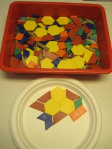 Pattern blocks displayed in a bin and offered with a paper plate for play